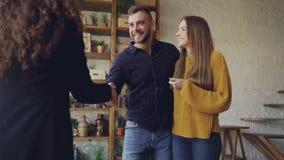 Замедленное движение агента снабжения жилищем давая ключи к покупателям новой квартиры, счастливый супруг и жена обнимающ и целую сток-видео