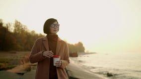 Замедленное движение азиатской женщины в пальто и eyeglasses идя на пляж на заходе солнца акции видеоматериалы