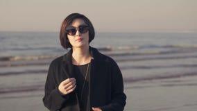 Замедленное движение азиатской женщины в пальто на предпосылке океанских волн видеоматериал