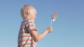 Замедленное движение белокурый мальчик закручивая игрушка и joyfully улыбки ветра сток-видео