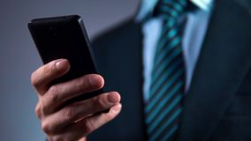 Замедленное движение, бизнесмен использует телефон и убивает его в его карманн куртки Стильный костюм акции видеоматериалы