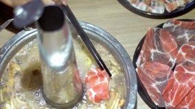 Замедленное движение владения сырого мяса говядины с палочками Китайское hotpot в Пекин акции видеоматериалы