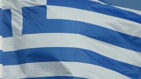 Замедленное движение греческого флага на поляке развевая над голубой предпосылкой акции видеоматериалы
