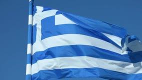 Замедленное движение греческого флага на поляке развевая над голубой предпосылкой сток-видео