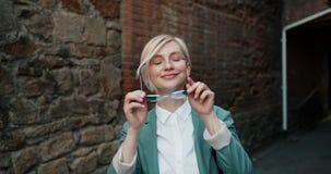 Замедленное движение жизнерадостной блондинкы принимая солнечные очки в усмехаться улицы акции видеоматериалы