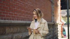 Замедленное движение жизнерадостной молодой женщины используя smartphone и идущ в улицу с кофе и наушниками Того самомоднейше сток-видео