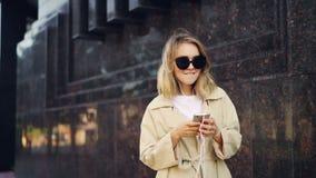 Замедленное движение жизнерадостных танцев молодой женщины в улице слушая к музыке с наушниками используя smartphone самомоднейше акции видеоматериалы