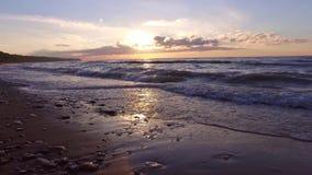 ЗАМЕДЛЕННОЕ ДВИЖЕНИЕ: Заход солнца океана Складывать развевает над пустым пляжем steadicam видеоматериал