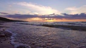ЗАМЕДЛЕННОЕ ДВИЖЕНИЕ: Заход солнца океана Складывать развевает над пустым пляжем steadicam акции видеоматериалы
