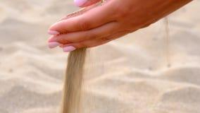 Замедленное движение, конец вверх: неизвестная шаловливая молодая женщина бросает пригорошню белого песка Время бежит как песок д сток-видео