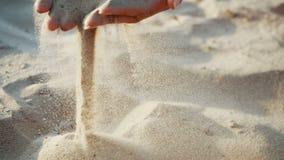 Замедленное движение, конец вверх: песок проходит через пальцы молодой женщины Песок бежит через пальцы a сток-видео