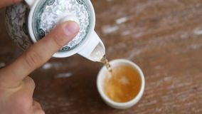 Замедленное движение лить здоровый зеленый чай от винтажного чайника в чашке на деревянном столе Церемония традиционного китайски сток-видео
