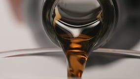 ЗАМЕДЛЕННОЕ ДВИЖЕНИЕ: Макрос снял лить коричневого напитка от стеклянной бутылки акции видеоматериалы