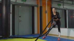 Замедленное движение маленькой девочки включено с веревочками в спортзале сток-видео
