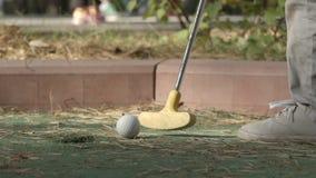 ЗАМЕДЛЕННОЕ ДВИЖЕНИЕ: Маленький игрок бьет шар для игры в гольф для того чтобы продырявить курс видеоматериал