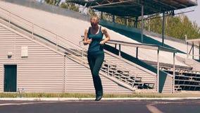 Замедленное движение: Молодая милая девушка, sporty физические данные, выполняет легкий бег через стадион видеоматериал