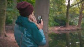 Замедленное движение молодая неузнаваемая девушка женщины в красных шляпе и синем пиджаке, в осени в парке около тяг озера сток-видео