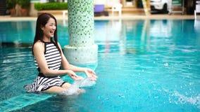 Замедленное движение молодой женщины брызгая воду в бассейне видеоматериал