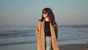 Замедленное движение молодой женщины в пальто на предпосылке океанских волн сток-видео
