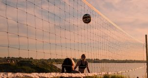 ЗАМЕДЛЕННОЕ ДВИЖЕНИЕ, НИЗКИЙ УГОЛ, КОНЕЦ ВВЕРХ, ПИРОФАКЕЛ СОЛНЦА: Атлетическая девушка играя скачки волейбола пляжа в воздухе и з акции видеоматериалы