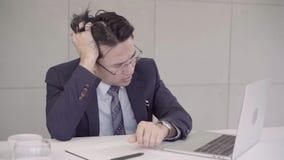 Замедленное движение - осадка бизнесмена на столе в офисе Азиатский бизнесмен будучи отжиманным путем работа в офисе сток-видео