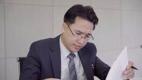 Замедленное движение - осадка бизнесмена на столе в офисе Азиатский бизнесмен будучи отжиманным путем работа в офисе