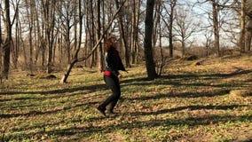 Замедленное движение прекрасная девушка в бегах черных кожаной куртки через древесины и расчистку усмехается красиво и поворачива видеоматериал