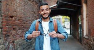 Замедленное движение привлекательного аравийского парня принимая солнечные очки усмехаясь outdoors сток-видео