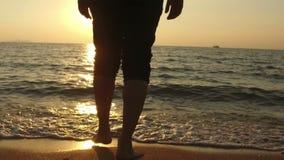 ЗАМЕДЛЕННОЕ ДВИЖЕНИЕ: прогулка человека на море и заход солнца сток-видео