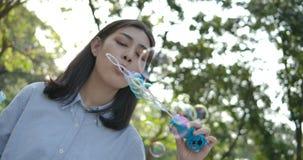 Замедленное движение пузыря молодой красивой азиатской женщины улыбок дуя на заходе солнца в парке сток-видео