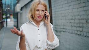 Замедленное движение радостной зрелой женщины говоря на мобильном телефоне стоя outdoors видеоматериал