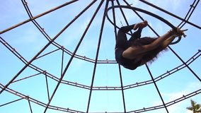 Замедленное движение снимая женщину в плотный висеть одежд и своды в кольце для воздушной акробатики видеоматериал