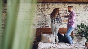 Замедленное движение счастливых молодых любовников танцуя на двуспальной кровати имея потеху в спальне и смеясь над халатно жизне сток-видео