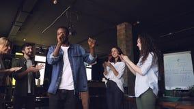 Замедленное движение танцев парня счастливого работника офиса Афро-американских на корпоративной партии пока его члены команды хл сток-видео