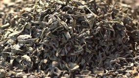 ЗАМЕДЛЕННОЕ ДВИЖЕНИЕ: Чай выходит падение на снятую кучу зеленого чая - макрос акции видеоматериалы