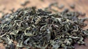 ЗАМЕДЛЕННОЕ ДВИЖЕНИЕ: Чай выходит падение на снятую кучу зеленого чая - макрос видеоматериал