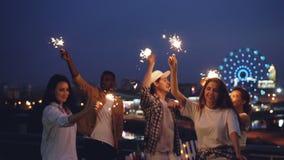 Замедленное движение excited людей танцуя с гореть света Бенгалии на партии крыши ночи и иметь потеху совместно видеоматериал