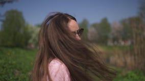 ЗАМЕДЛЕННОЕ ДВИЖЕНИЕ 120fps: Девушка женщины молодого счастливого коричневого цвета путешественника с волосами усмехаясь и повора видеоматериал