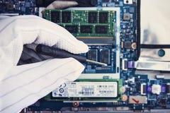 Замена памяти в компьтер-книжке, в одном из пунктов обслуживания для ремонта компьтер-книжек рука в белой перчатке держит screwdr стоковые фотографии rf