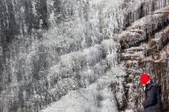 Замерзая водопад который летел от горы с туристом та нося красная шляпа на Lachen Северный Сикким, Индия Стоковые Фото