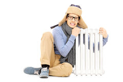 Замерзая молодой парень в шляпе и шарфе зимы сидя рядом с radia Стоковое фото RF