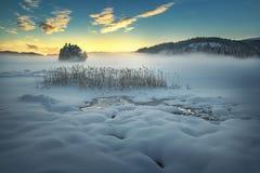 Замерли озеро Jonsvatnet около Тронхейма, Норвегии Свет захода солнца над собирать туман стоковые изображения