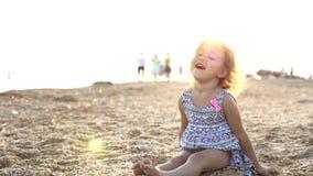 Замедленное движение маленькой девочки сидя на песке пляжа, смеяться над и бросать акции видеоматериалы