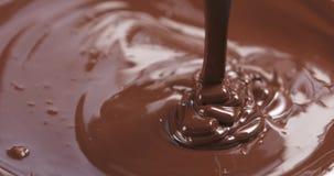 Замедленное движение наградной темноты расплавило шоколад будучи политым от ложки в правой части рамки Стоковая Фотография
