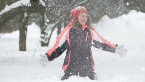 Замедленное движение радостного ребенка играя в снеге Счастливая девушка имея потеху вне зимнего дня акции видеоматериалы