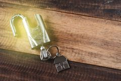 Замок, ключ и дом формируют ключевую бирку на деревянном столе стоковое изображение