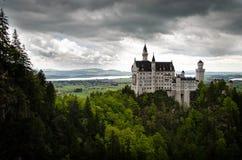 Замок Нойшванштайна: Драматические облачные небеса с деревней в предпосылке Стоковое Изображение