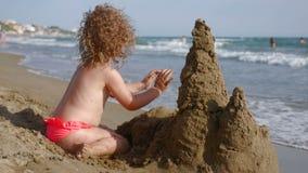 Замок песка здания маленькой девочки на пляже сток-видео
