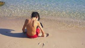 Замок песка здания подростка на тропическом пляже сток-видео