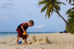 Замок песка здания мальчика на тропическом пляже Стоковое Изображение RF
